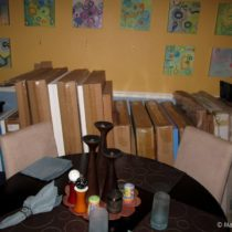 Another view of large canvases and drawings stuffed in the dining room